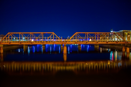 A golden rail bridge reflects off of the Des Moines River