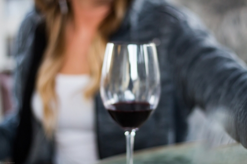 An out of focus shot of a glass of wine in front of a female subject
