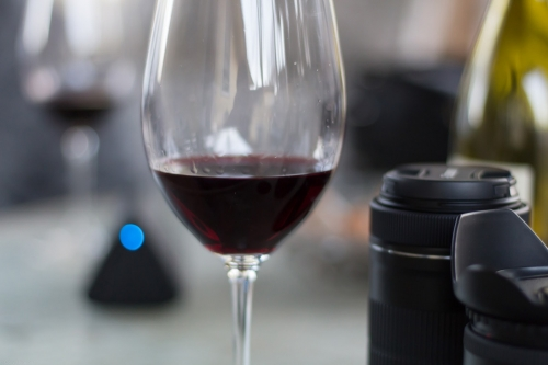 A wine showing tears next to a camera lens